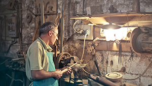 Mann arbeitet an beleuchteter Werkbank