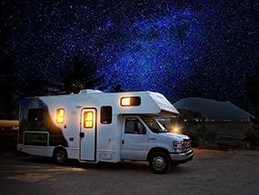 Erleuchtetes Wohnmobil vor Sternenhimmel