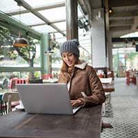 Frau mit Mütze arbeitet im Wintergarten eines Cafés am Laptop