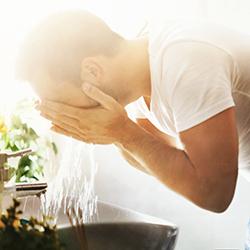 Mann wäscht sein Gesicht am Waschbecken im Badezimmer vor dem Spiegel