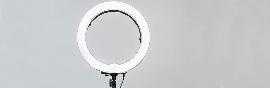 Ringförmige LED-Röhre auf Stativ mit grauem Hintergrund